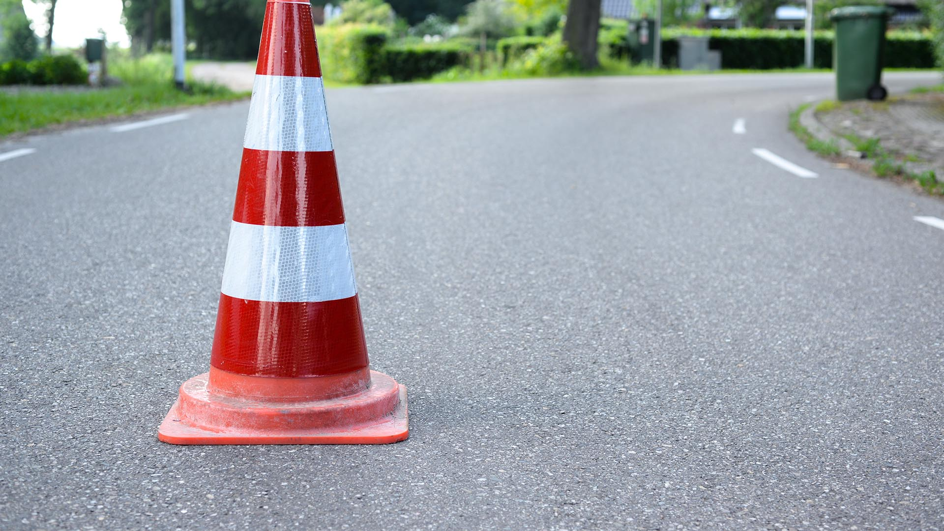one orange hazard cone in middle of the roadway